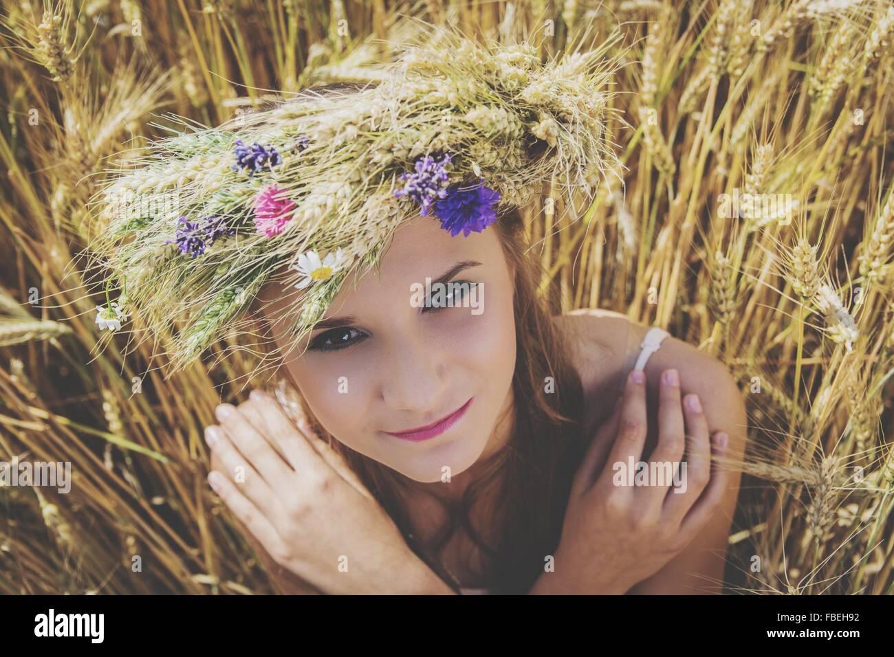 Retrato de joven Bella portando flores en la cabeza en el campo Imagen De Stock
