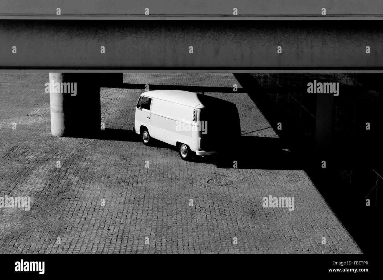Ángulo de visión baja de Van bajo el edificio en el Estacionamiento Foto de stock