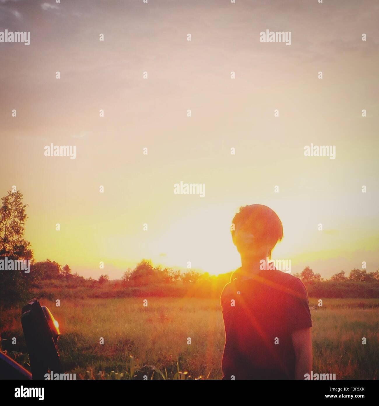 Iluminada desde atrás hombre permanente en el campo durante la puesta de sol Imagen De Stock