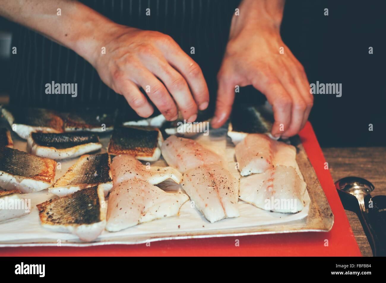 Recortada de manos del chef con carne de pescado en cocina comercial Imagen De Stock