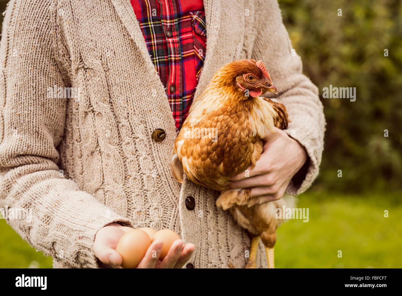 Hombre sujetando la gallina y el huevo Imagen De Stock