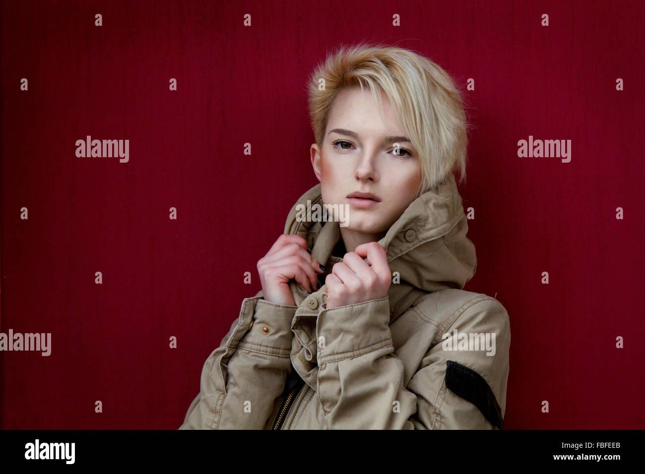 Retrato de joven mujer vistiendo Chaqueta mientras está de pie contra la pared roja Imagen De Stock