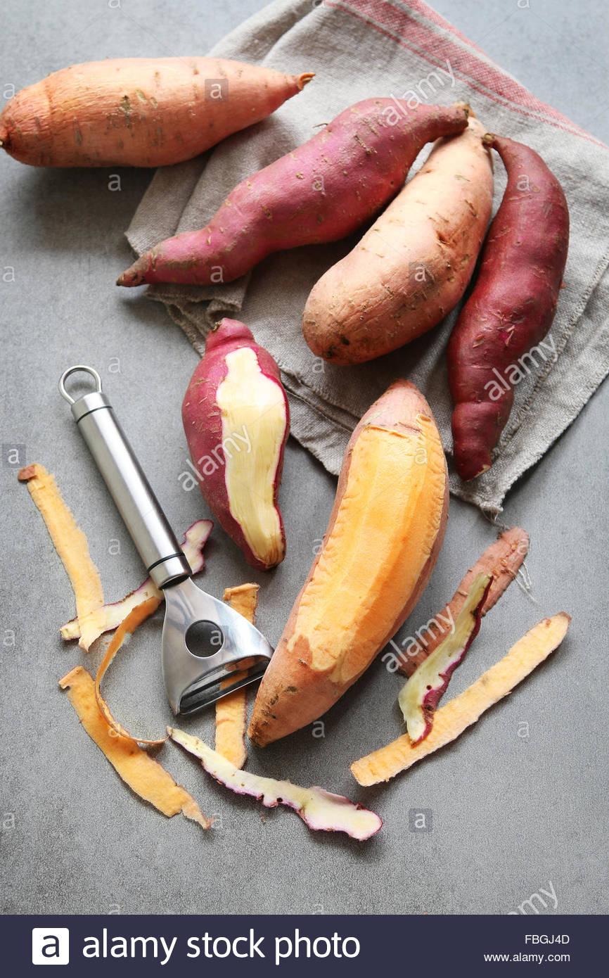 Naranja y rojo japonés batatas sobre fondo gris Imagen De Stock
