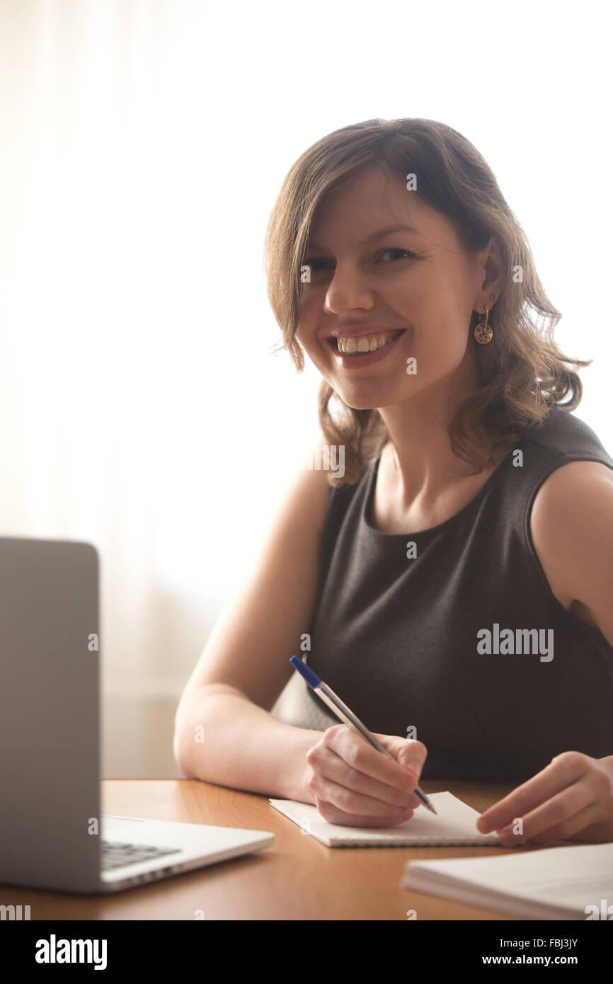 Amable sonriente joven sentado delante de un ordenador portátil, la oficina o estudiante mujer en desgaste formal, Foto de stock