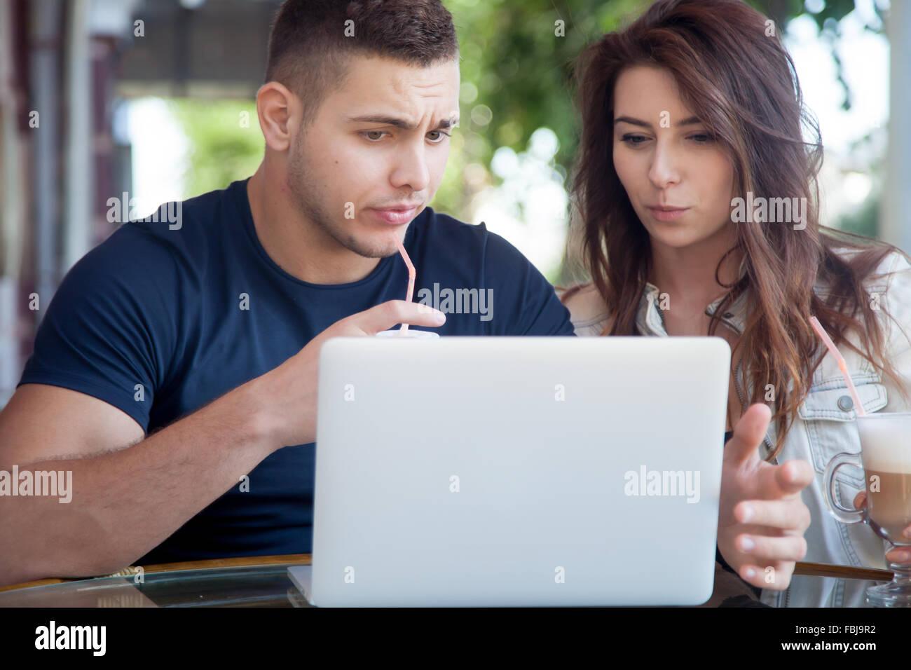 Cándido retrato de hombre joven y mujer en ropa casual sentado en la cafetería de la calle, utilizando Imagen De Stock