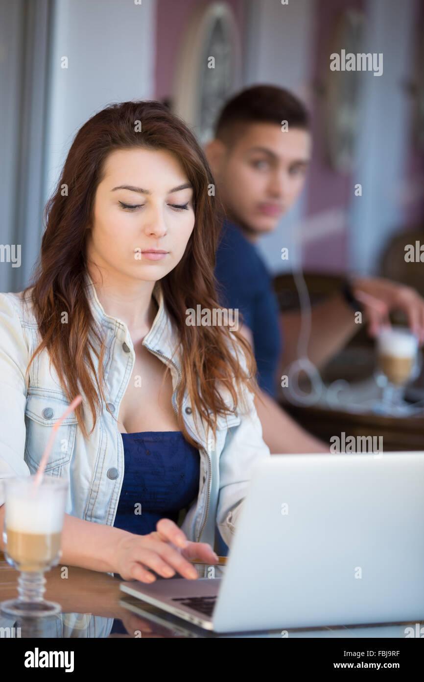 Hermosa joven grave en ropa casual sentado en la cafetería de la calle trabajando en el portátil mientras Imagen De Stock