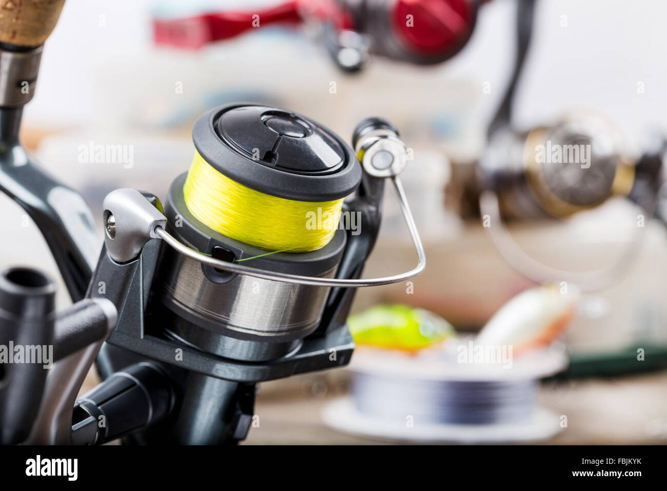 Closeup caña de pescar con carrete sobre fondo de aborda en cajas con cebos, señuelos, wobblers Imagen De Stock