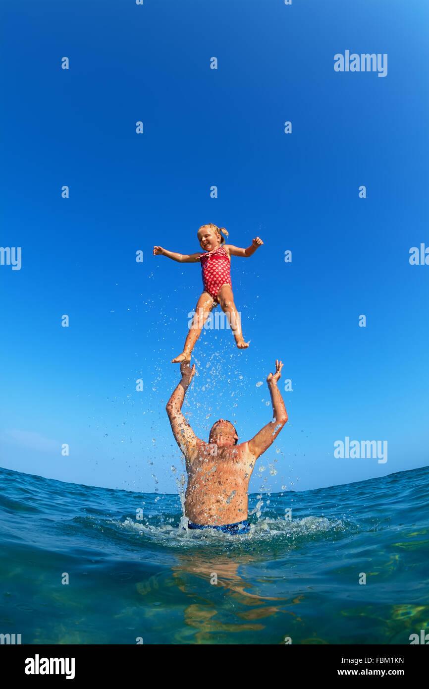 Abuelo tirando hacia arriba el aire de alta con salpicaduras de agua alegre niña en la playa. Actividad infantil Imagen De Stock