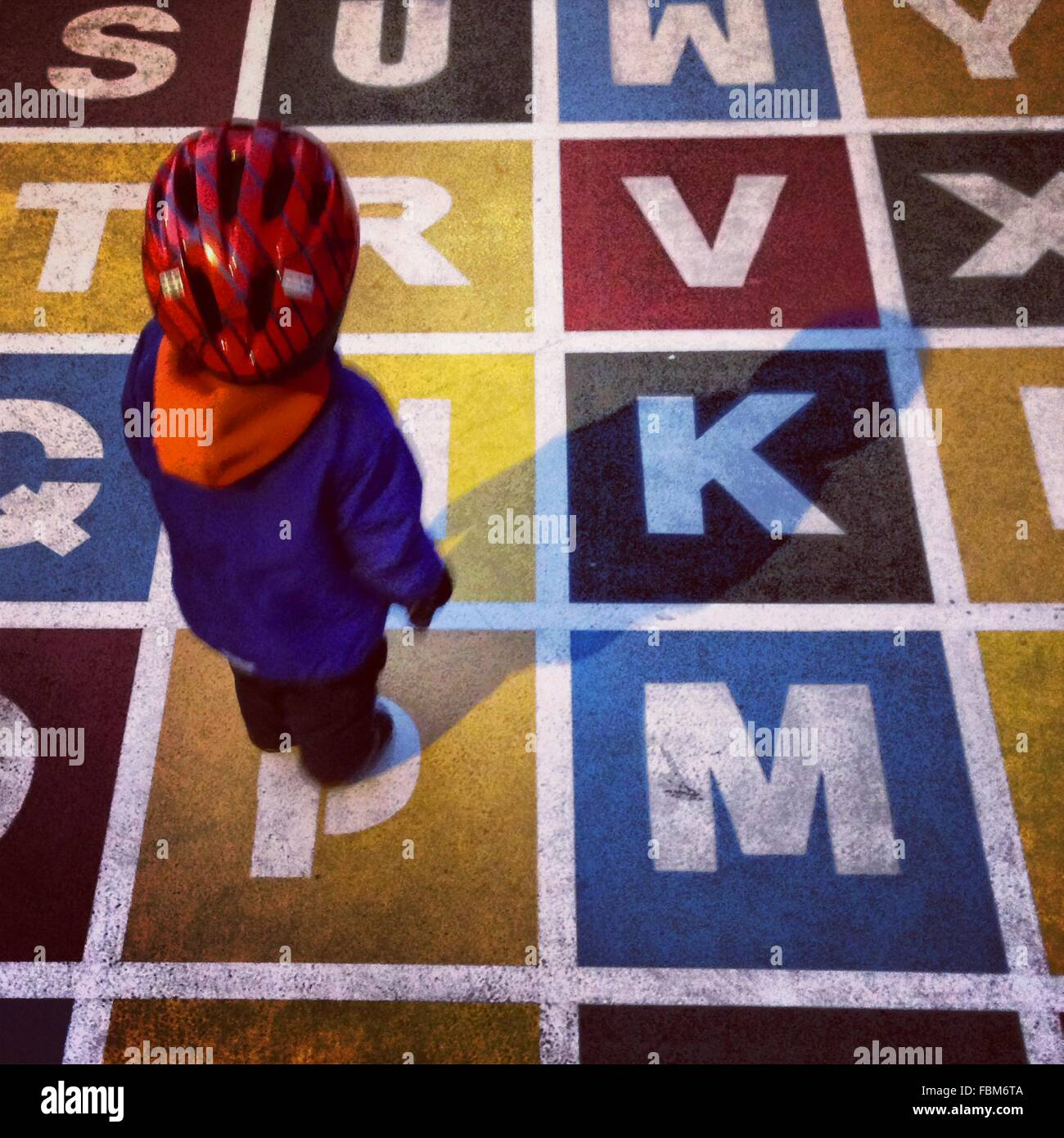 Un alto ángulo de visualización del hijo de pie en la pintura de los alfabetos Imagen De Stock