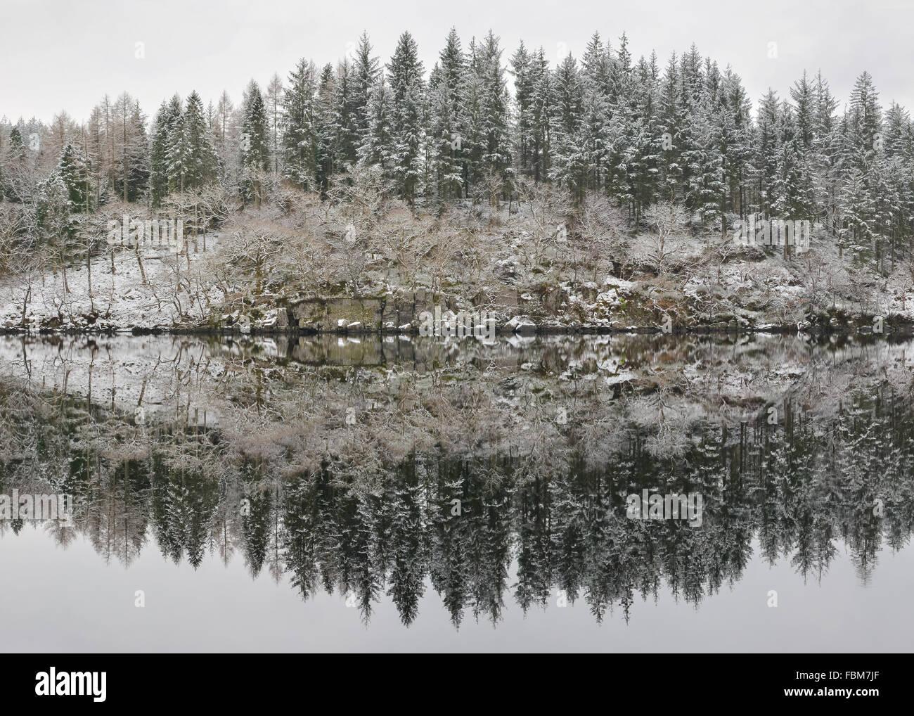 Loch Ard reflexiones después de las nevadas de invierno - una luz copo de nieve y agua creando reflejos sorprendentemente Imagen De Stock