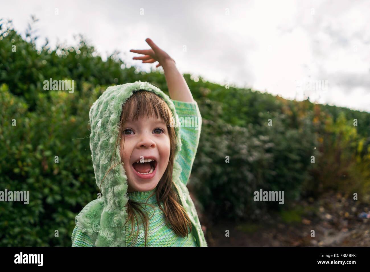 Emocionada chica con el brazo levantado en la lluvia Foto de stock