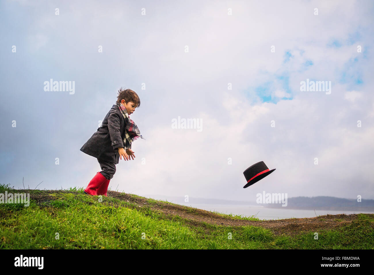 Boy persiguiendo su sombrero soplar lejos en el viento Imagen De Stock