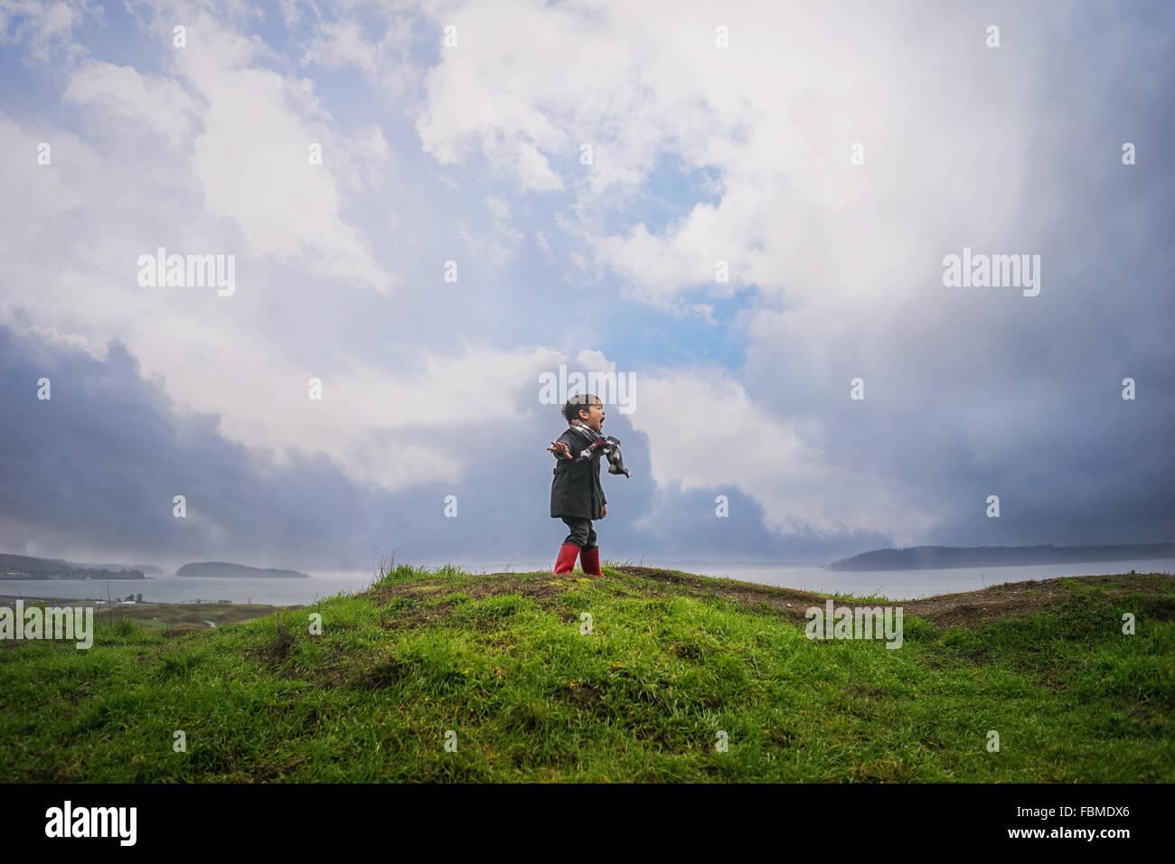 Niño de pie sobre una colina gritando Foto de stock
