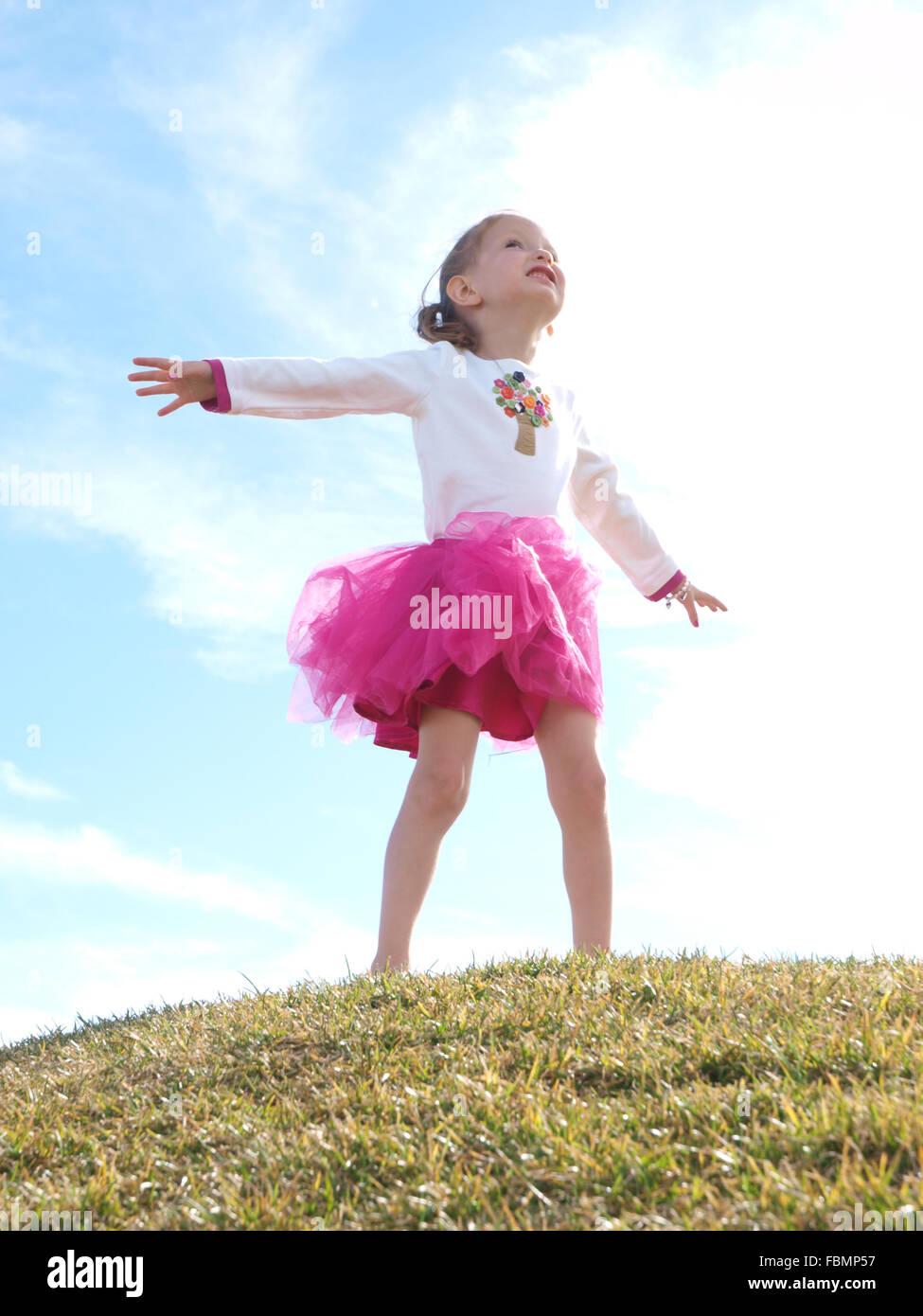 Chica de pie con los brazos extendidos Imagen De Stock