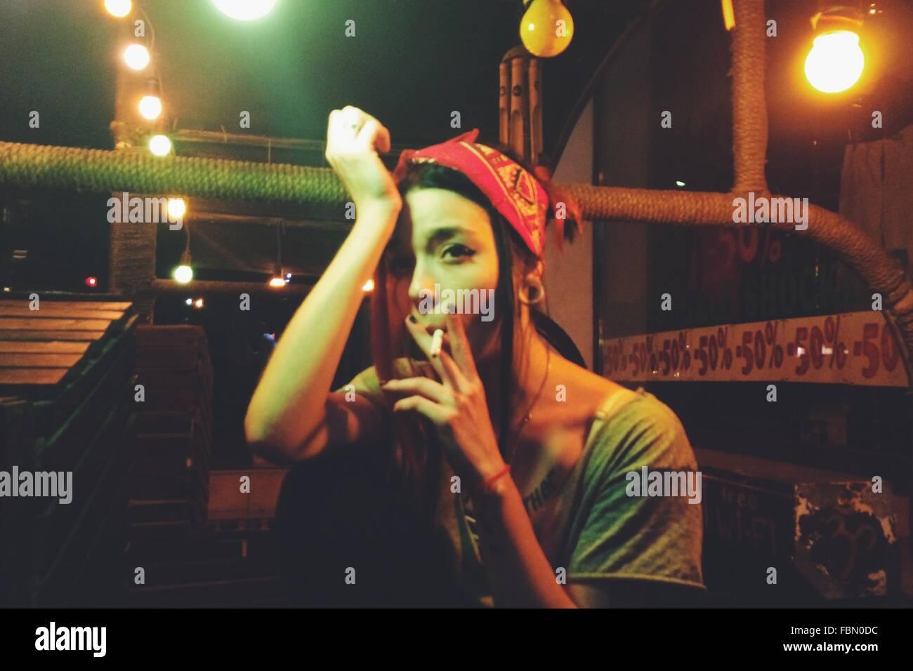 Mujer joven con la cabeza en la mano de fumar mientras se está sentado en la terraza iluminada Imagen De Stock