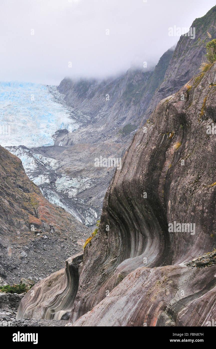 Patrones tallados en las paredes de roca de esquisto vertical en el glaciar Franz Josef como receeds debido al deshielo Imagen De Stock