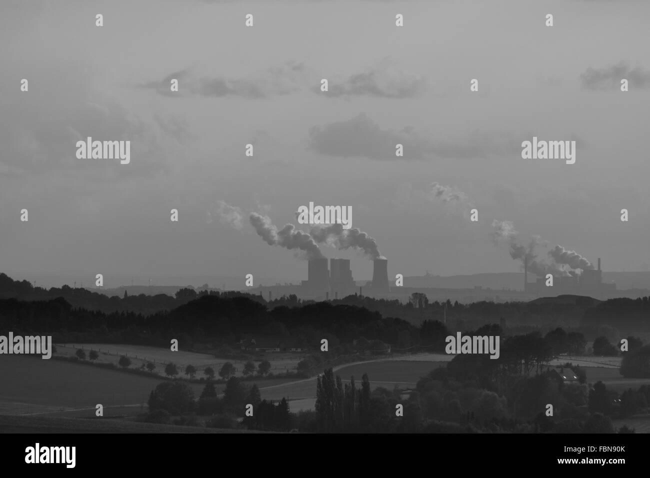 Distancia media vista de fábrica que emite humo contra el cielo Foto de stock