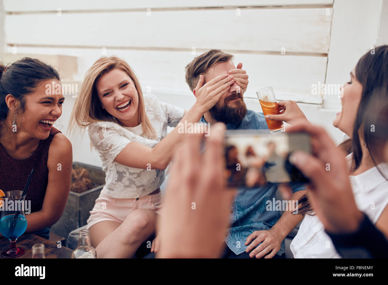 Grupo de Amigos divirtiéndose en una fiesta con un hombre tomando una foto en un teléfono inteligente. Los jóvenes disfrutando un partido juntos. Foto de stock