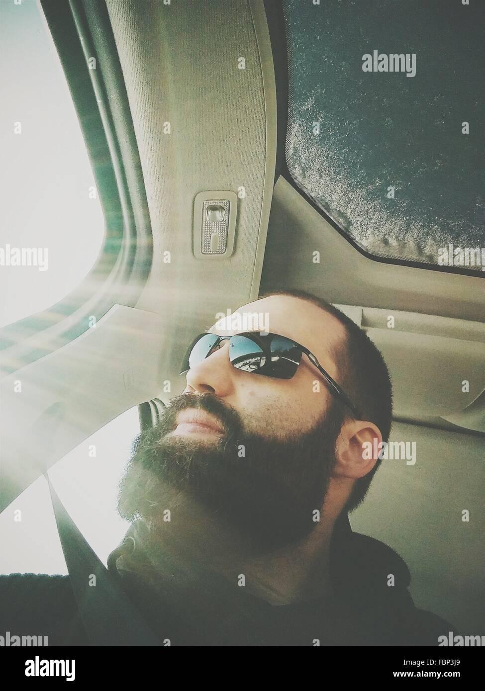 Ángulo de visión baja de joven con gafas de sol mientras está sentado en el coche Imagen De Stock