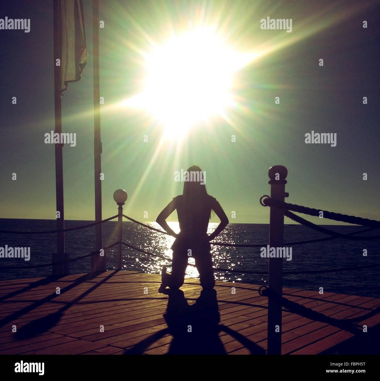 La luz del sol cayendo encima de la mujer arrodillada en el borde del embarcadero Imagen De Stock