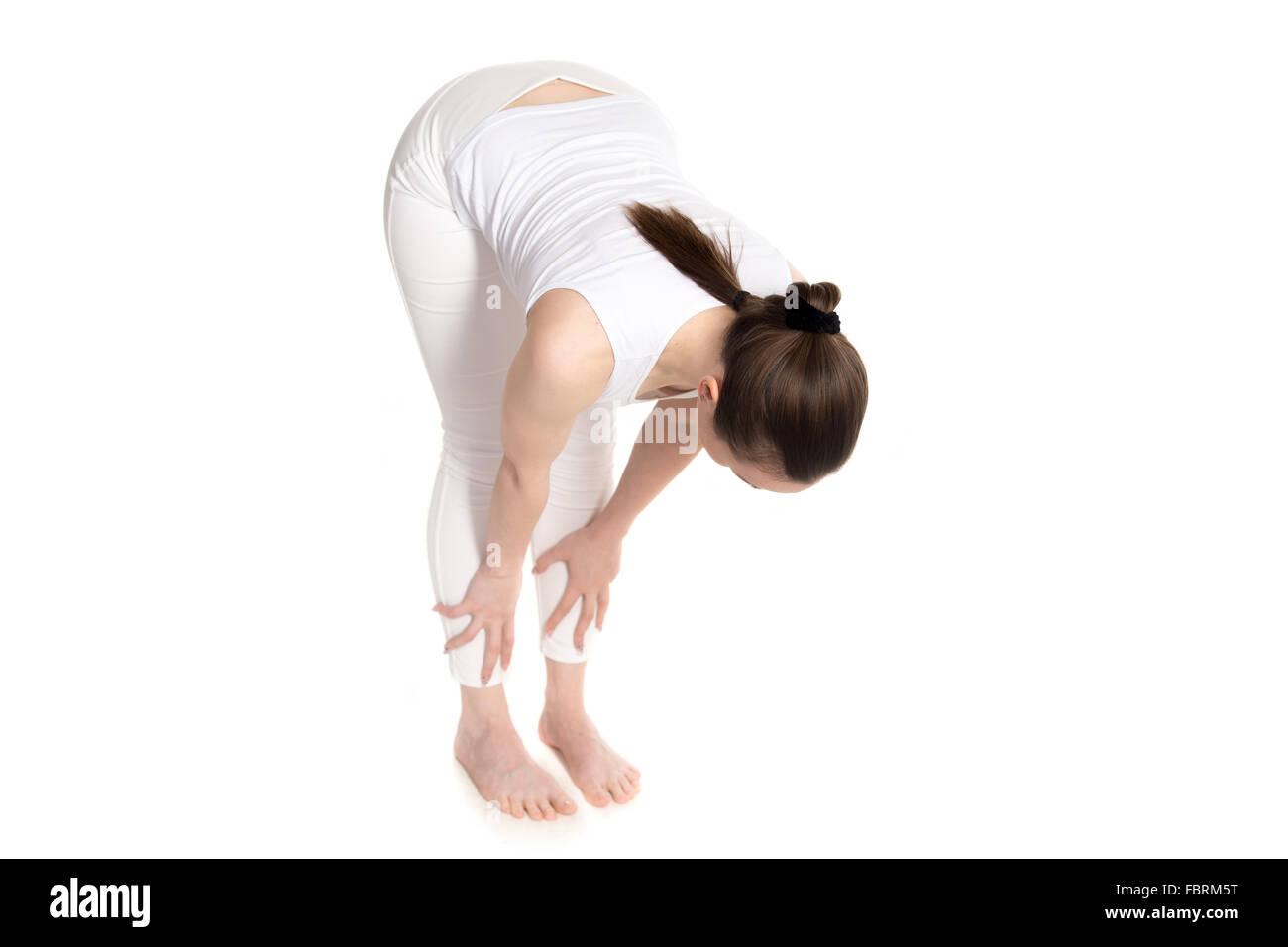Hermosa joven deportivo en blanco sportswear haciendo la mitad de flexión hacia adelante para la columna vertebral Imagen De Stock