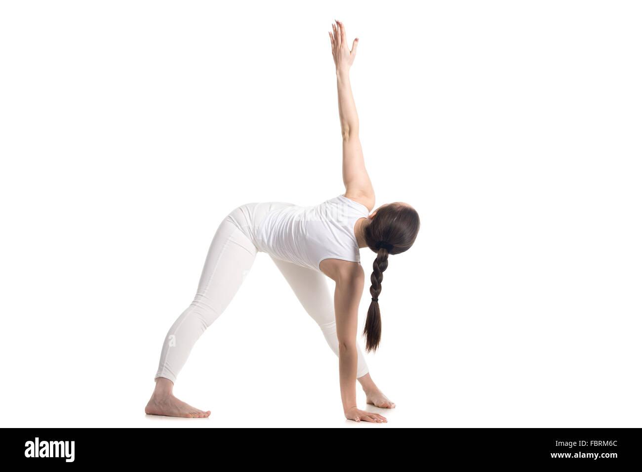 Hermosa joven deportivo en blanco permanente de ropa deportiva en una variación del triángulo pose, yoga Imagen De Stock