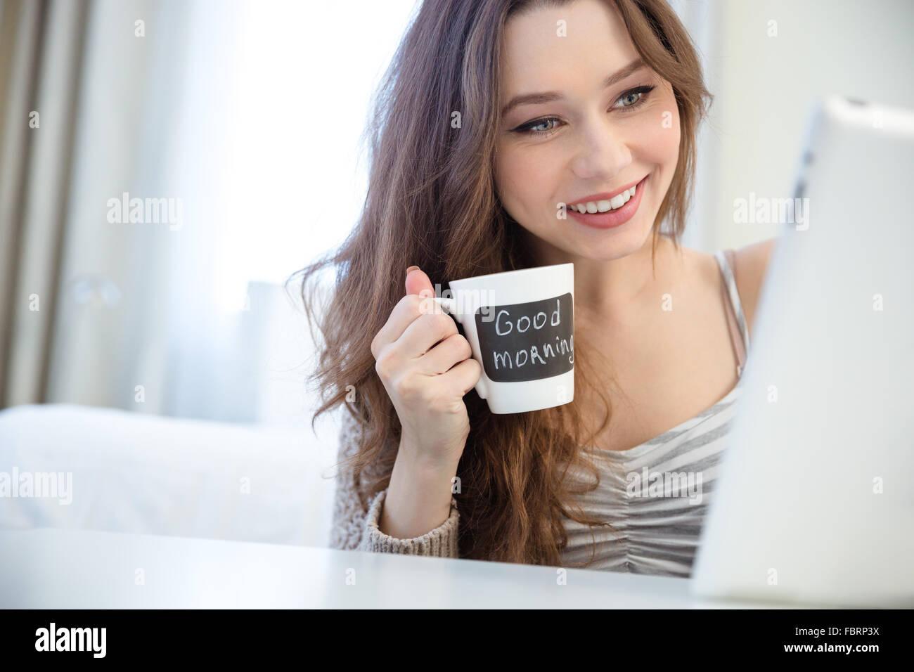 Sonriente joven encantador con tablet y bebiendo café de taza blanca con esfera negra para escribir Imagen De Stock