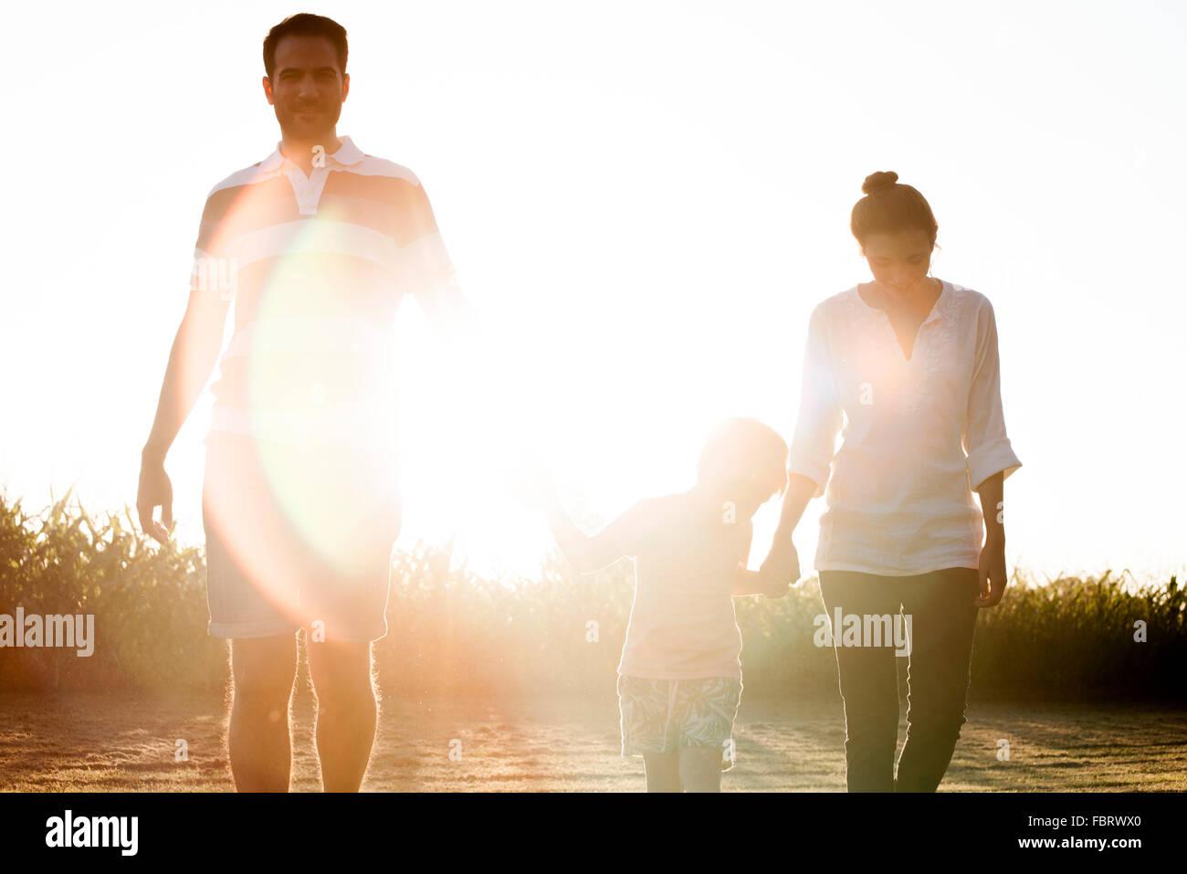 Familia con muchachito caminando juntos al aire libre Imagen De Stock