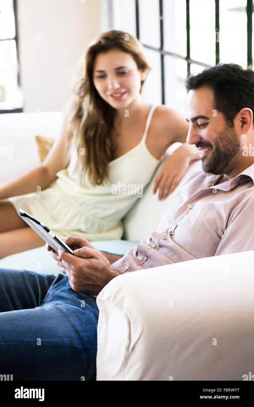 Pareja utilizando tablet digital en casa Imagen De Stock