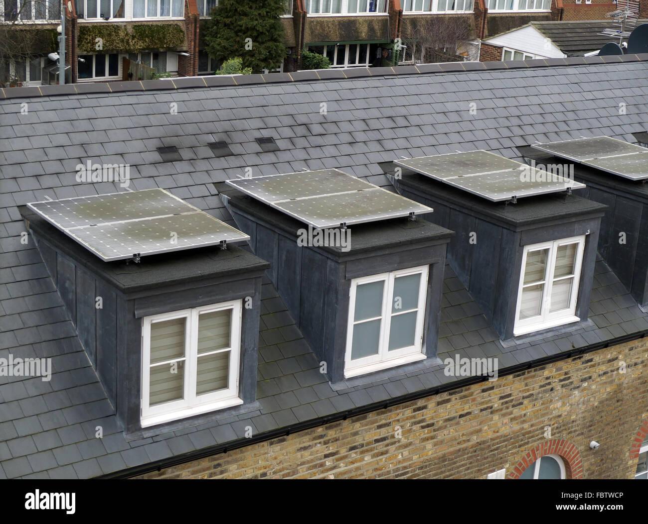 Sucio de paneles solares en tejados abuhardilladas, Brentford, Londres, Reino Unido. En necesidad de limpieza. Imagen De Stock