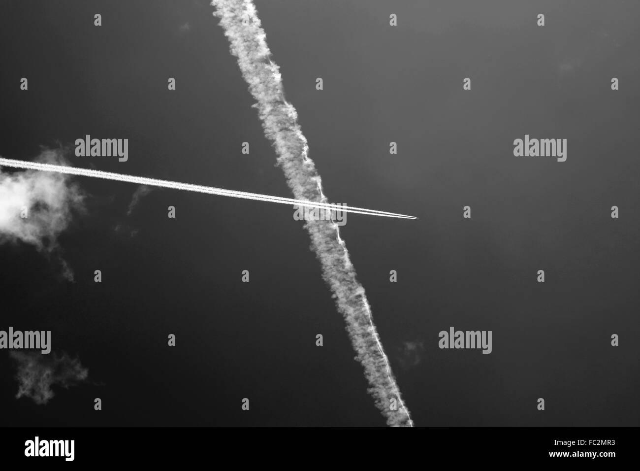 Avión de pasajeros senderos cruzando en un cielo azul Foto de stock