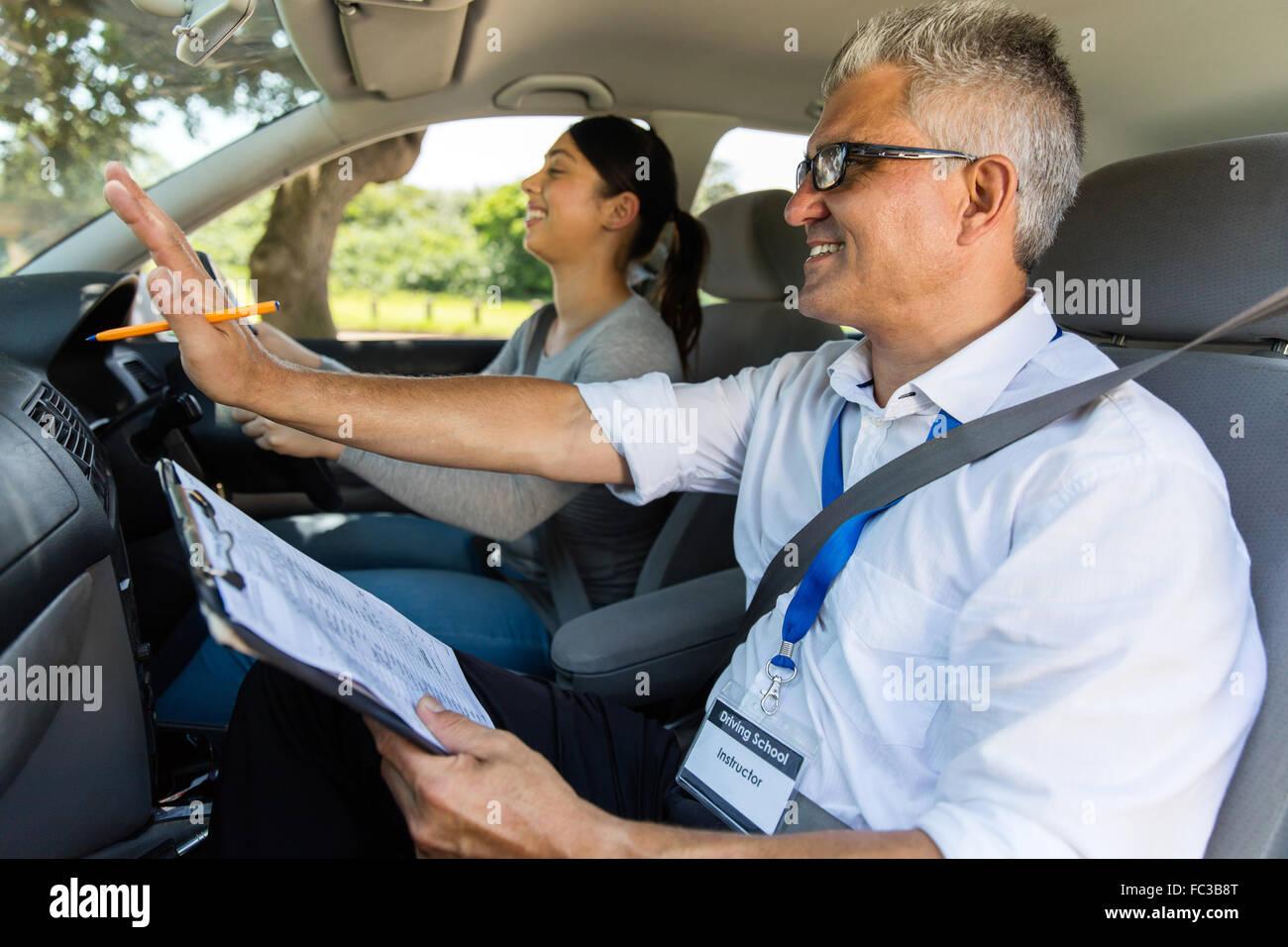 Sonriente joven con instructor de conducción tomar lecciones Imagen De Stock