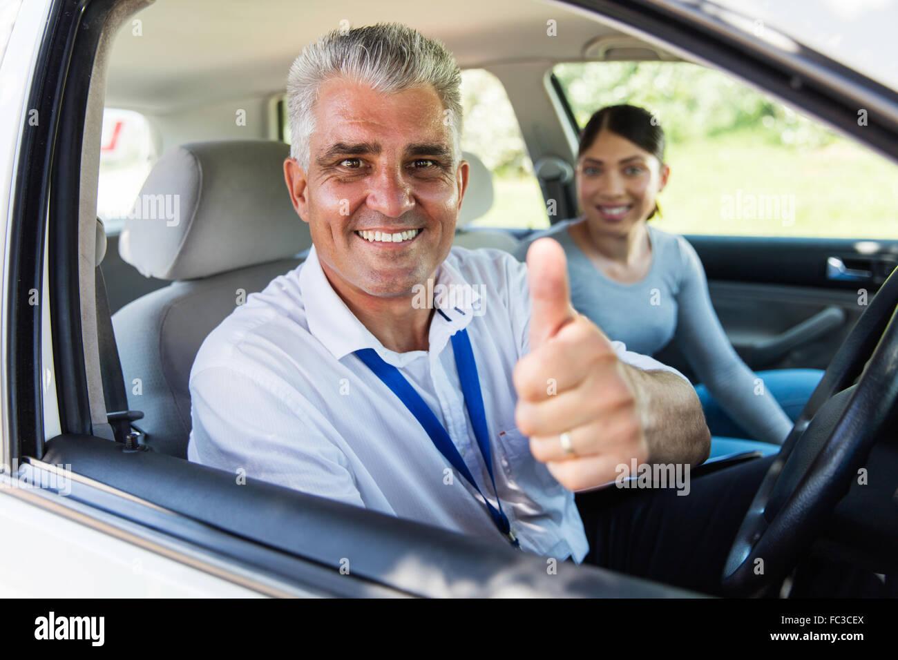 Guapo instructor de conducción superiores dando pulgar arriba Imagen De Stock