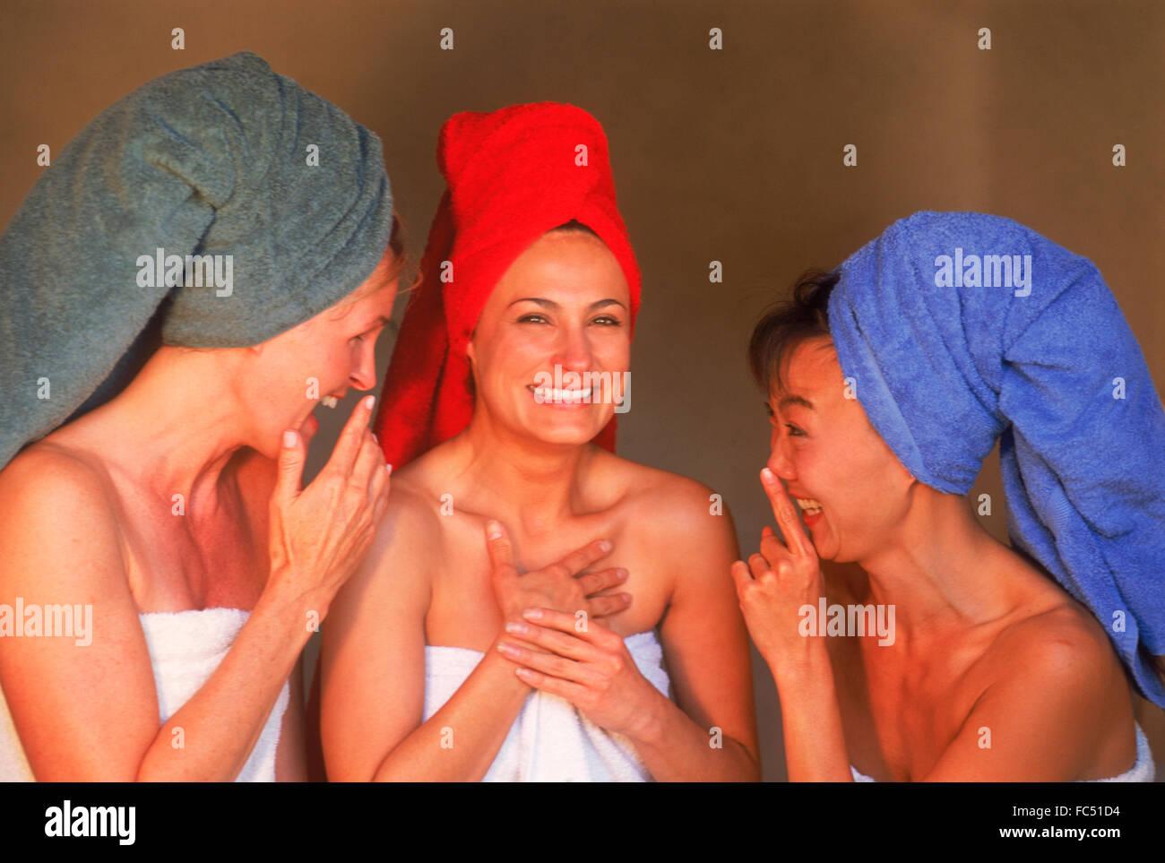 Tres mujeres de mezcla étnica con coloridas toallas de baño Compartir chismes y riendo Imagen De Stock