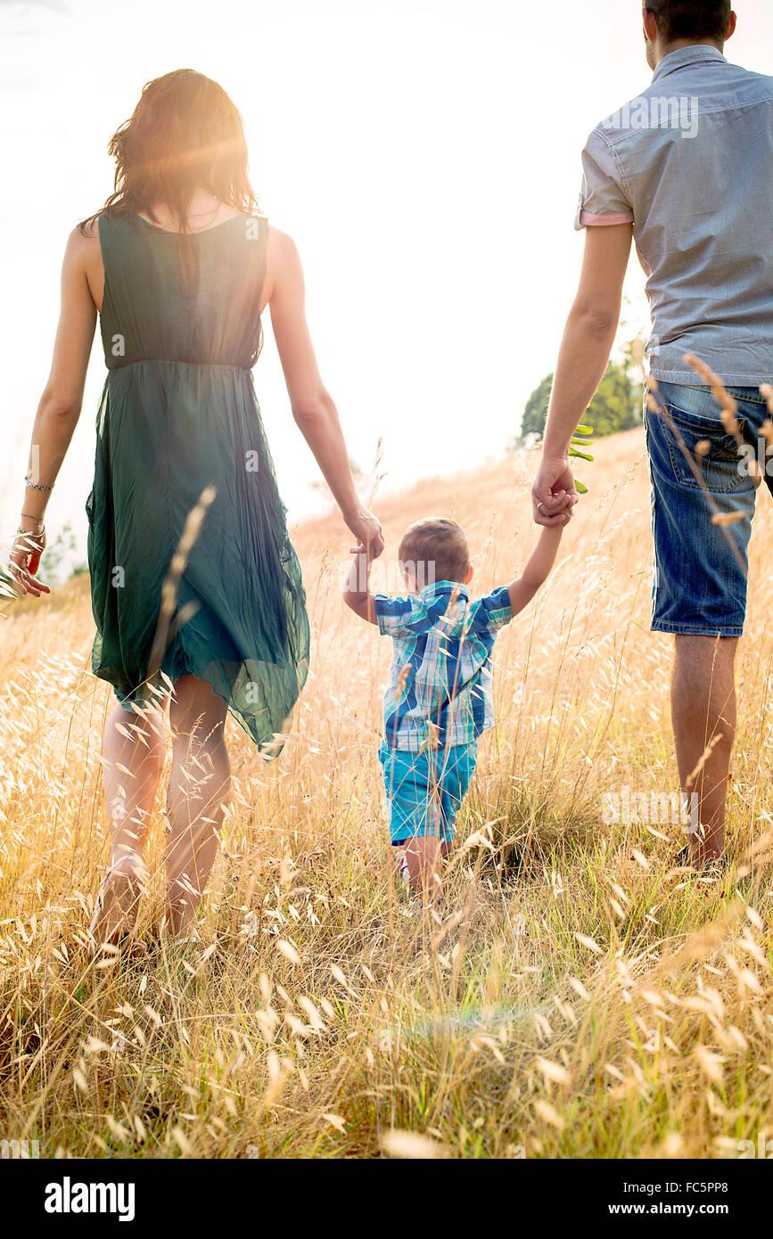 Los padres caminando con un hijo joven en el campo, vista trasera Imagen De Stock
