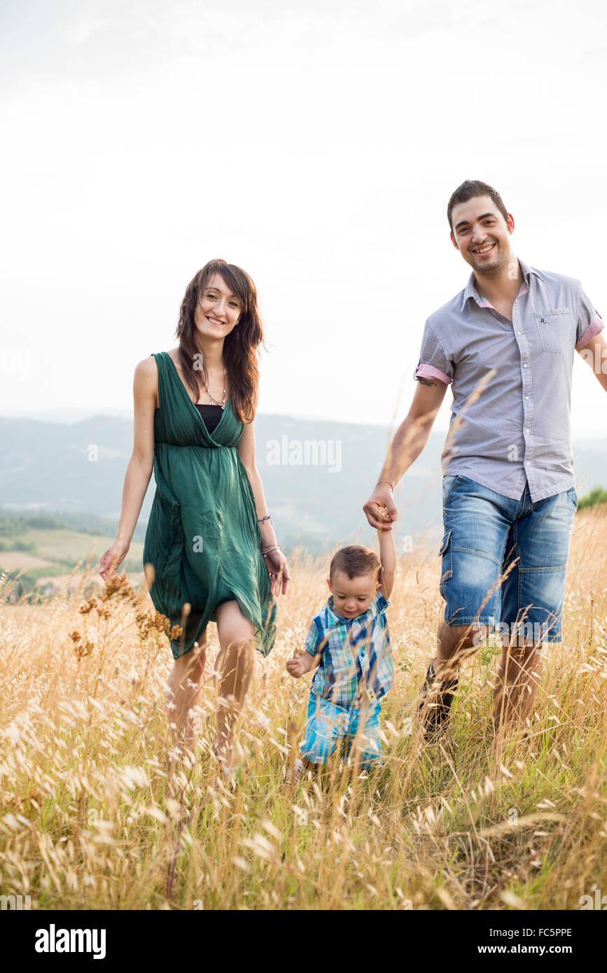Los padres sonrientes caminando con un hijo joven en el campo Imagen De Stock