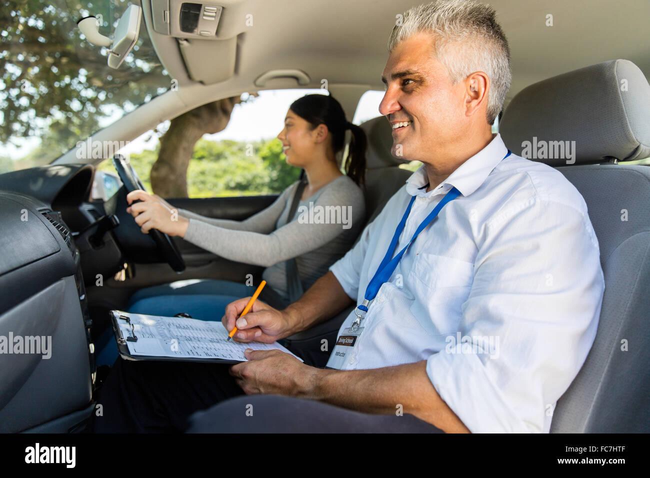 Joven tomando pruebas de conducción con instructor Imagen De Stock
