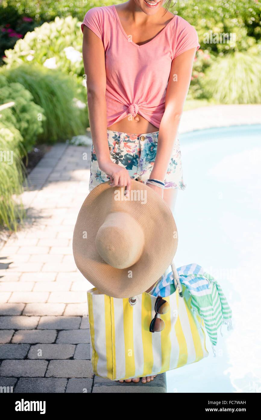 Mujer caucásica con sombrero para el sol y bolso Foto de stock