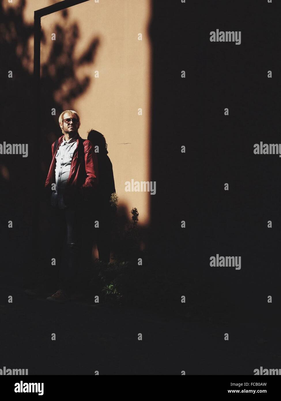 La longitud total del hombre de pie en la calle Imagen De Stock