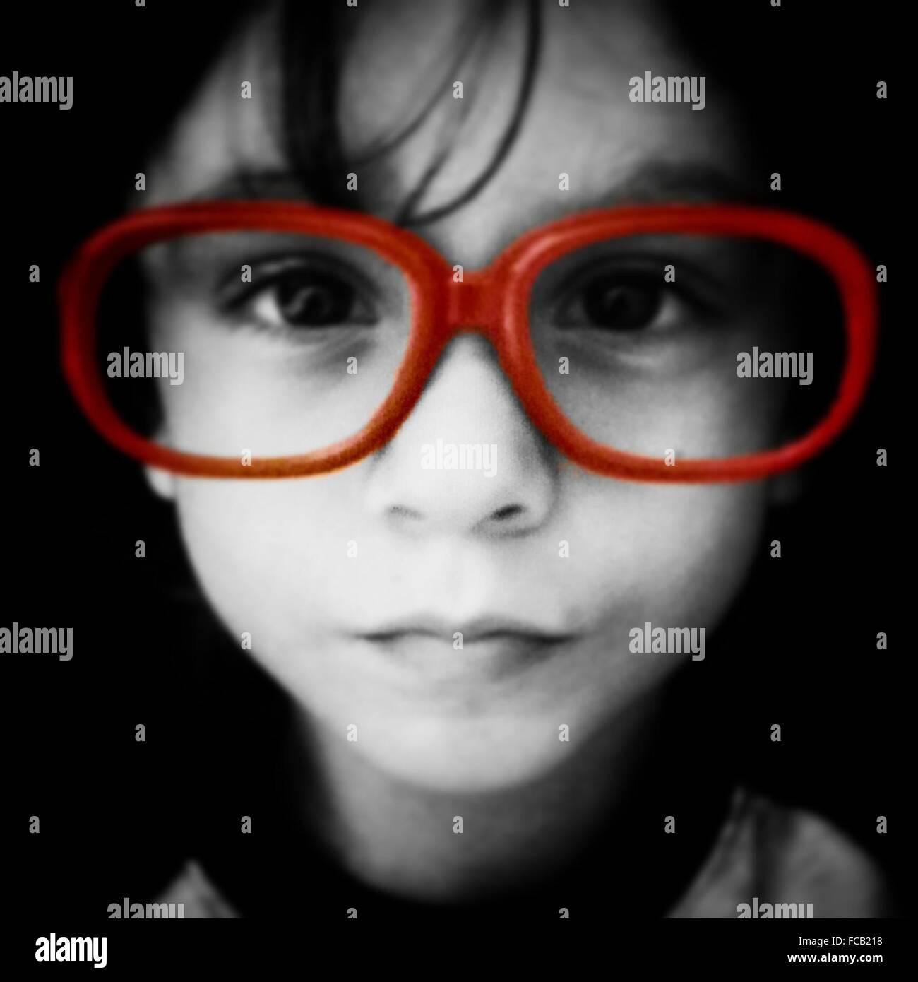 Niño usando anteojos ribeteado rojo grande Foto de stock