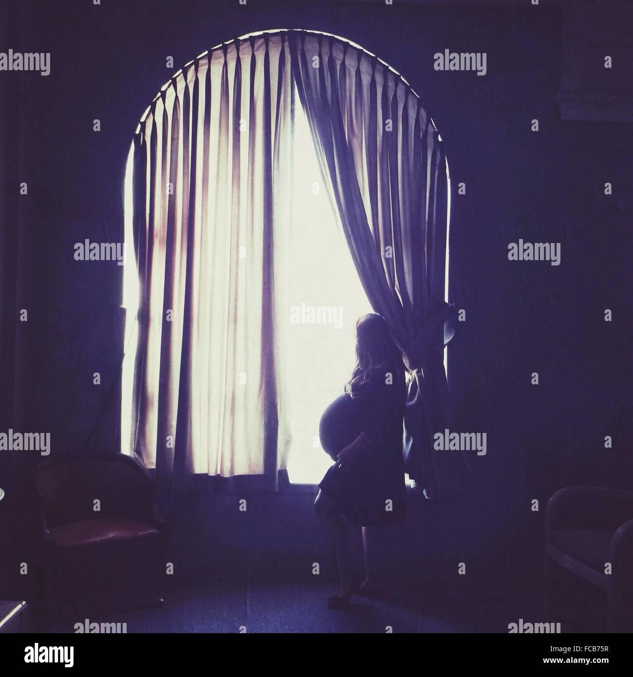 Vista lateral de la mujer embarazada mirando por la ventana en casa Imagen De Stock
