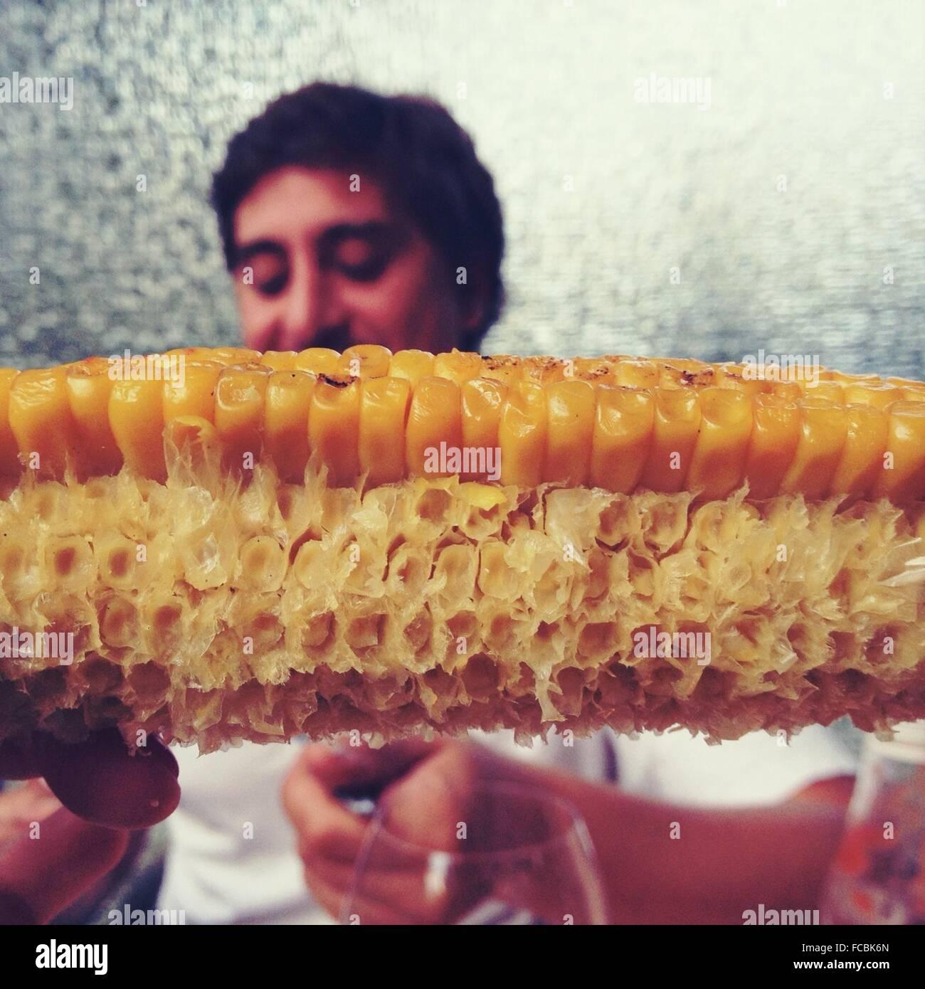Detalle de comerse el maíz con el hombre en segundo plano. Imagen De Stock