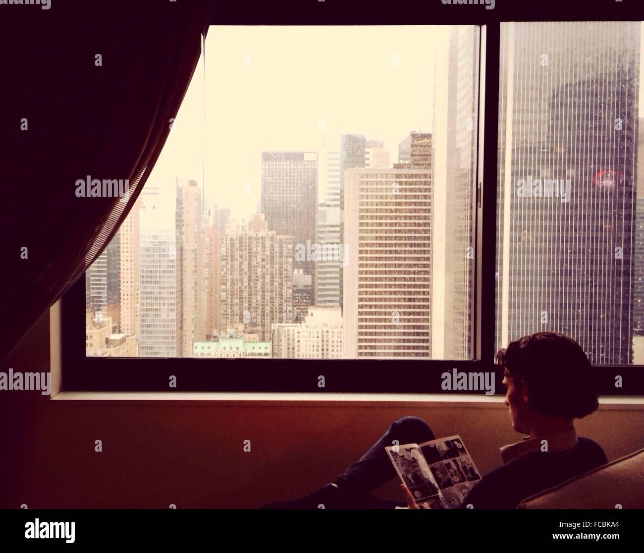 Vista trasera del hombre leyendo la revista en la casa por la ventana Imagen De Stock