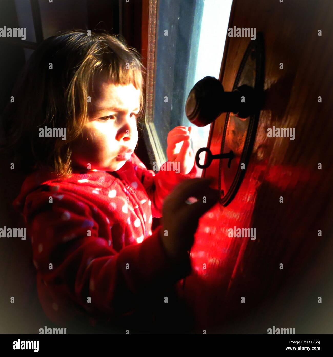 Cute Girl abrir la puerta con llaves en casa Imagen De Stock