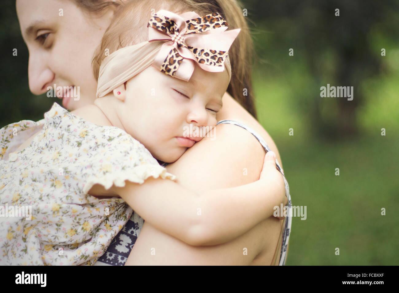 Vista lateral en primer plano de una madre de llevar al bebé al aire libre Imagen De Stock