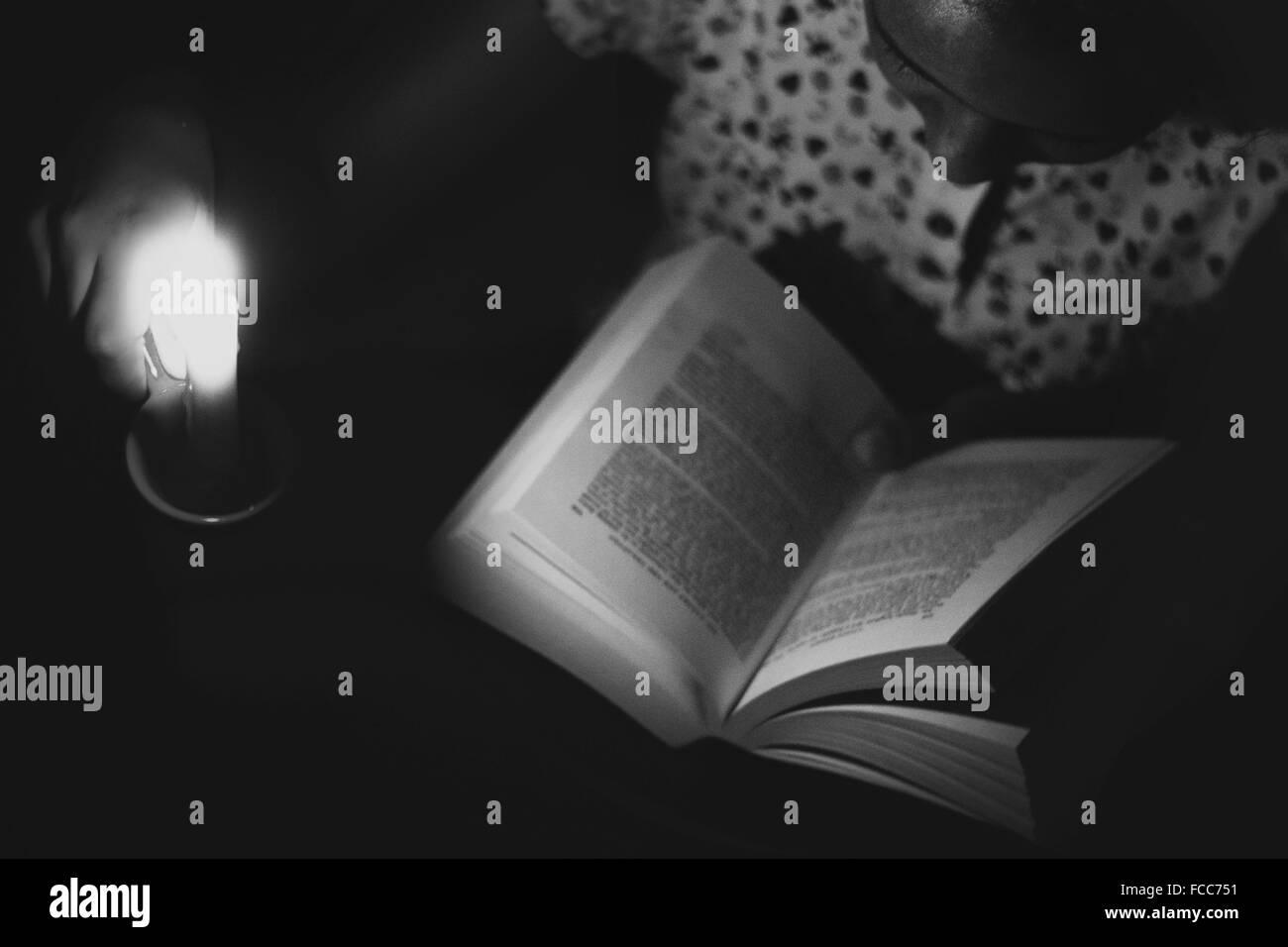 En primer plano un alto ángulo de vista de una niña libro de lectura en la oscuridad. Foto de stock