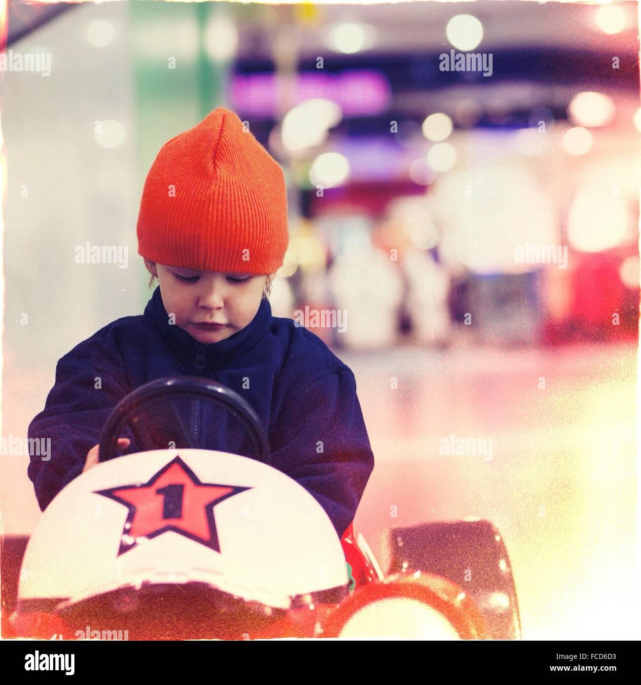 Primer plano de una chica conduciendo un coche de juguete Imagen De Stock