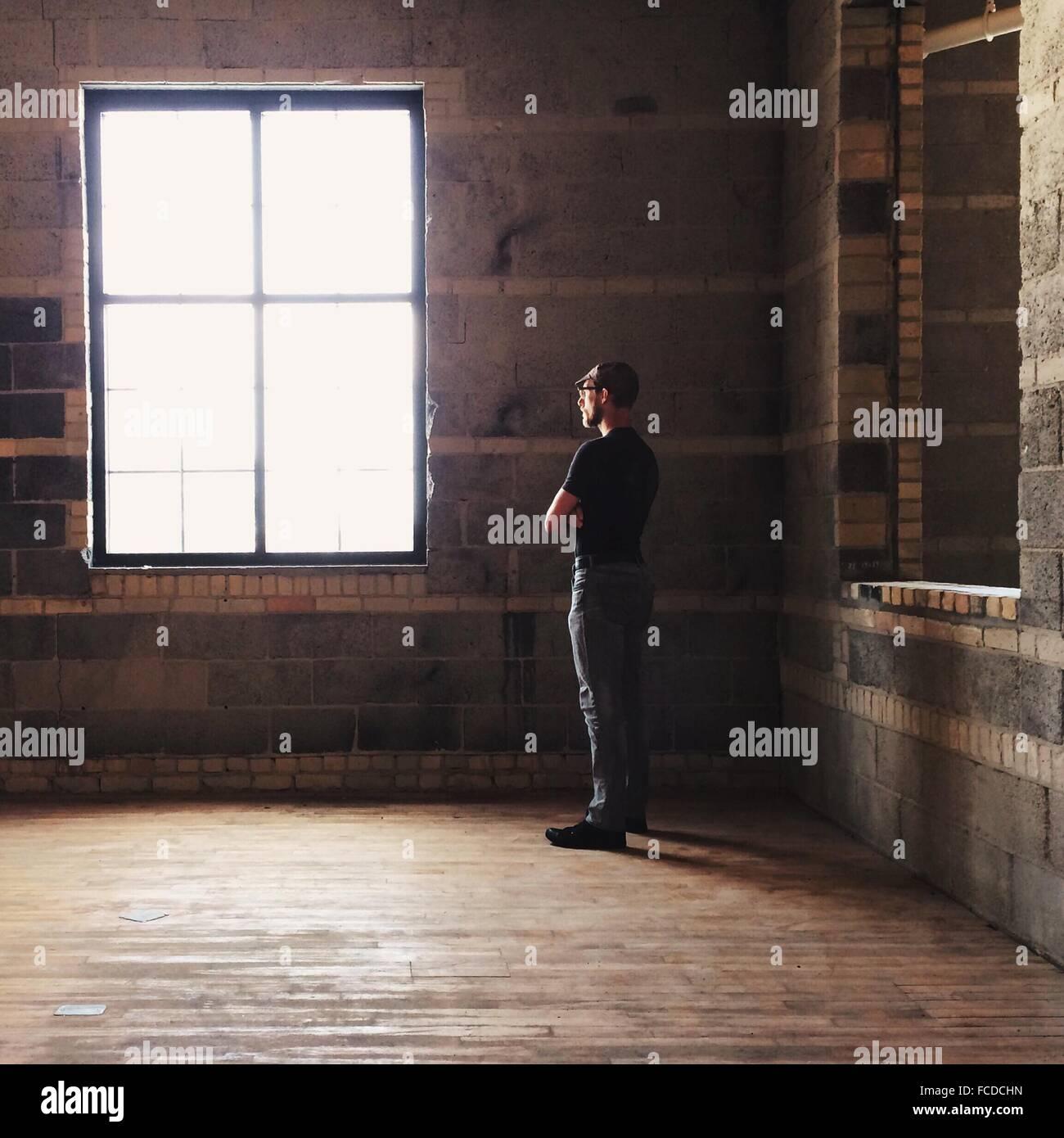 El perfil lateral de un hombre mirando hacia afuera de la ventana Foto de stock