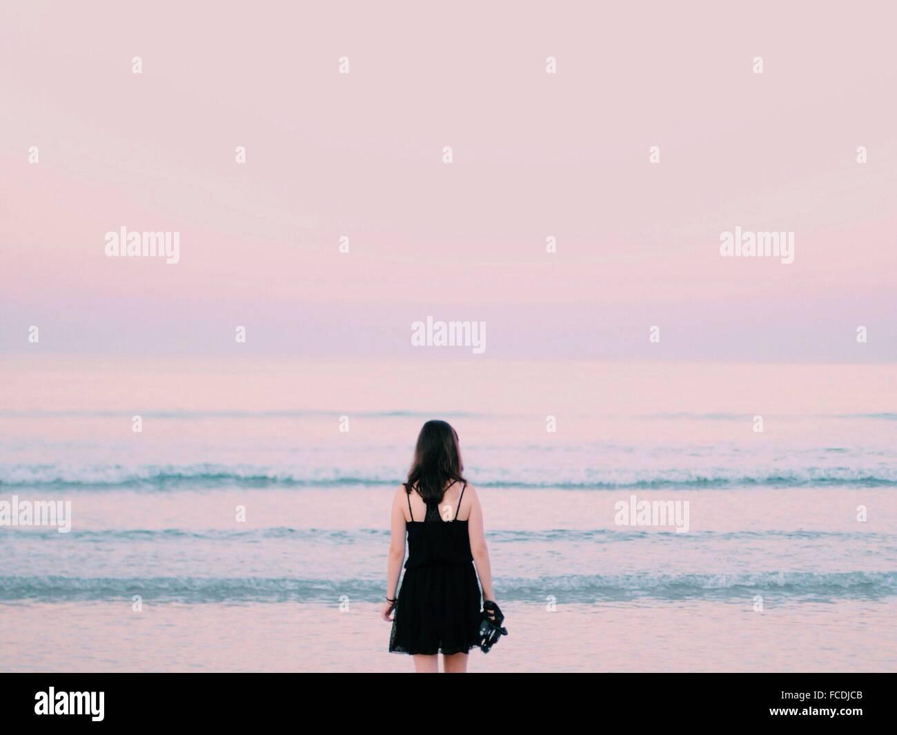Vista trasera de la mujer con vistas mar en calma Imagen De Stock