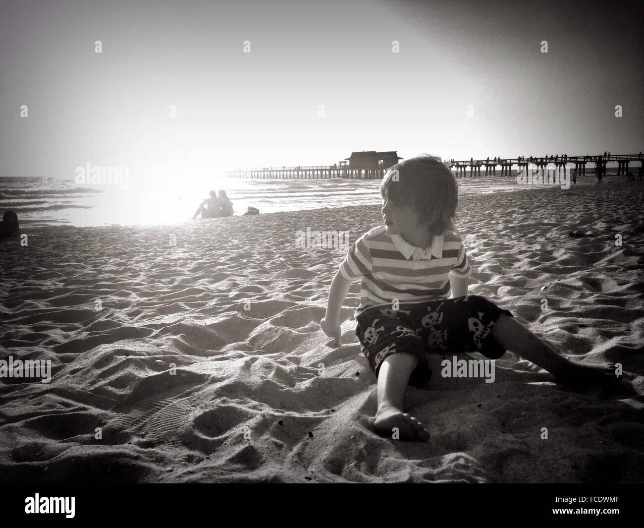 Muchacho sentado en la playa Imagen De Stock